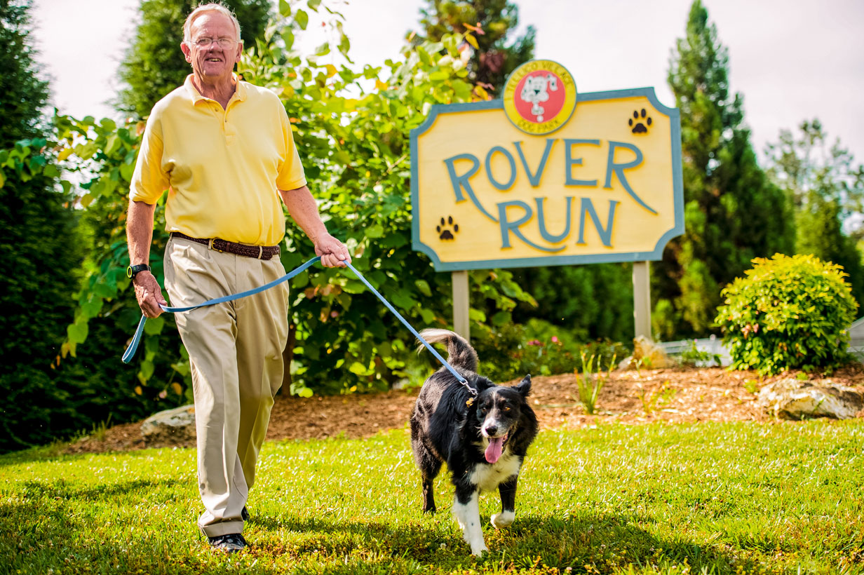 Villager walking his dog by the Rover Run park sign.