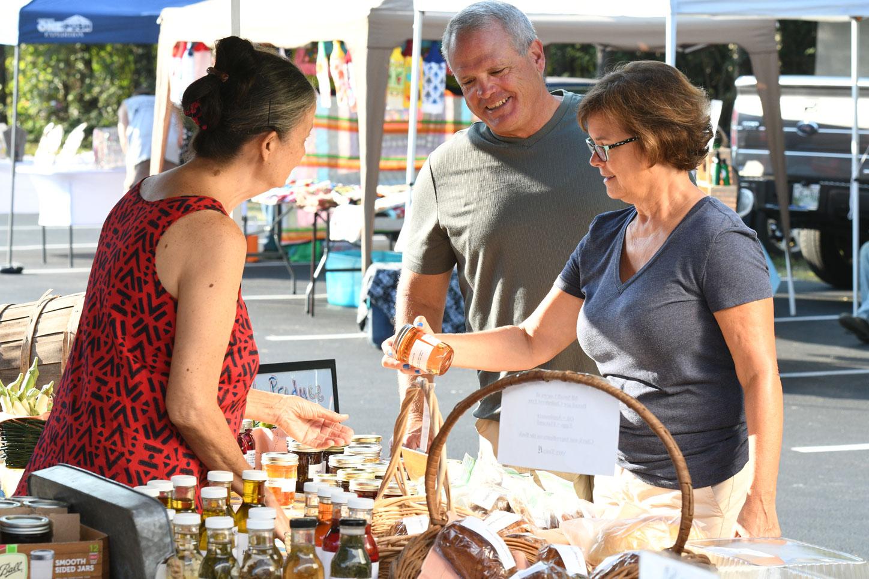 Tellico Village couple talking to a vendor at the farmer's market.