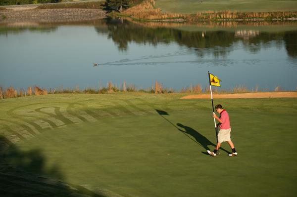 Tanasi Golf Course, man carrying a golf flag.
