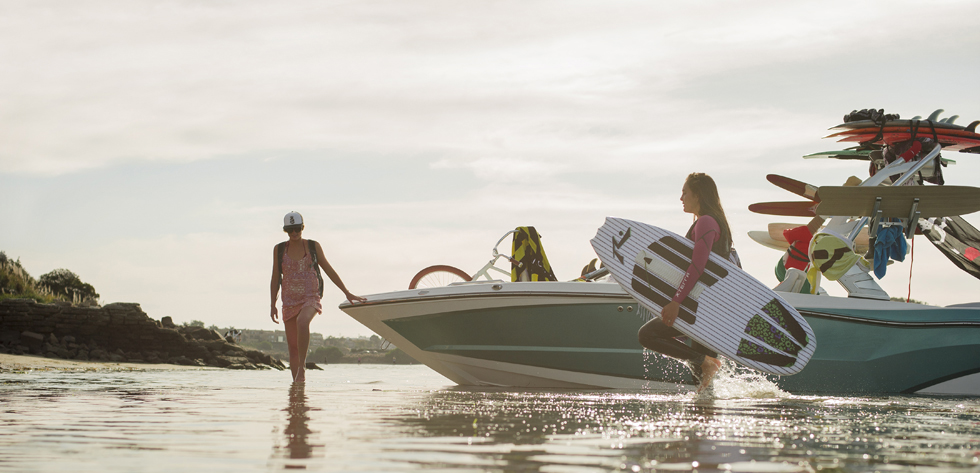 Young women preparing to wakeboard on the lake.