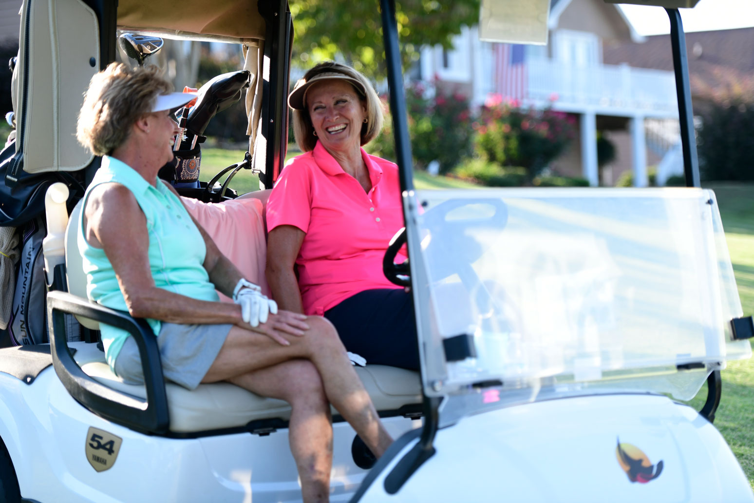 Ladies in the golf cart enjoying a conversation while taking a break from golfing.