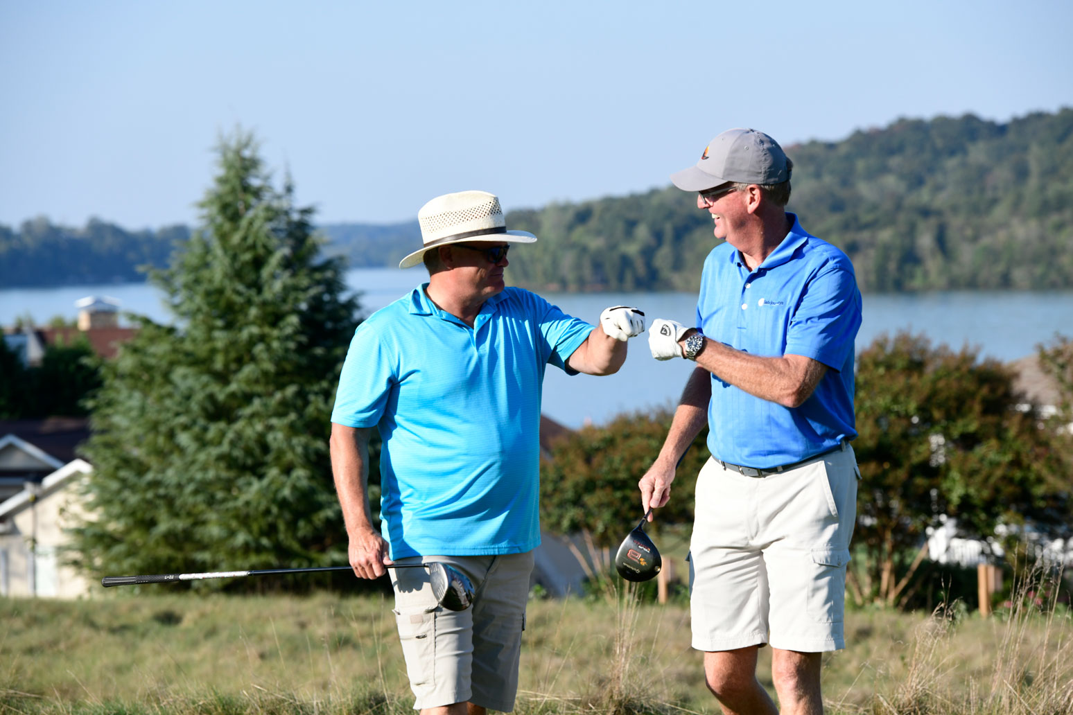 Men share a fist bump while on the golf course.