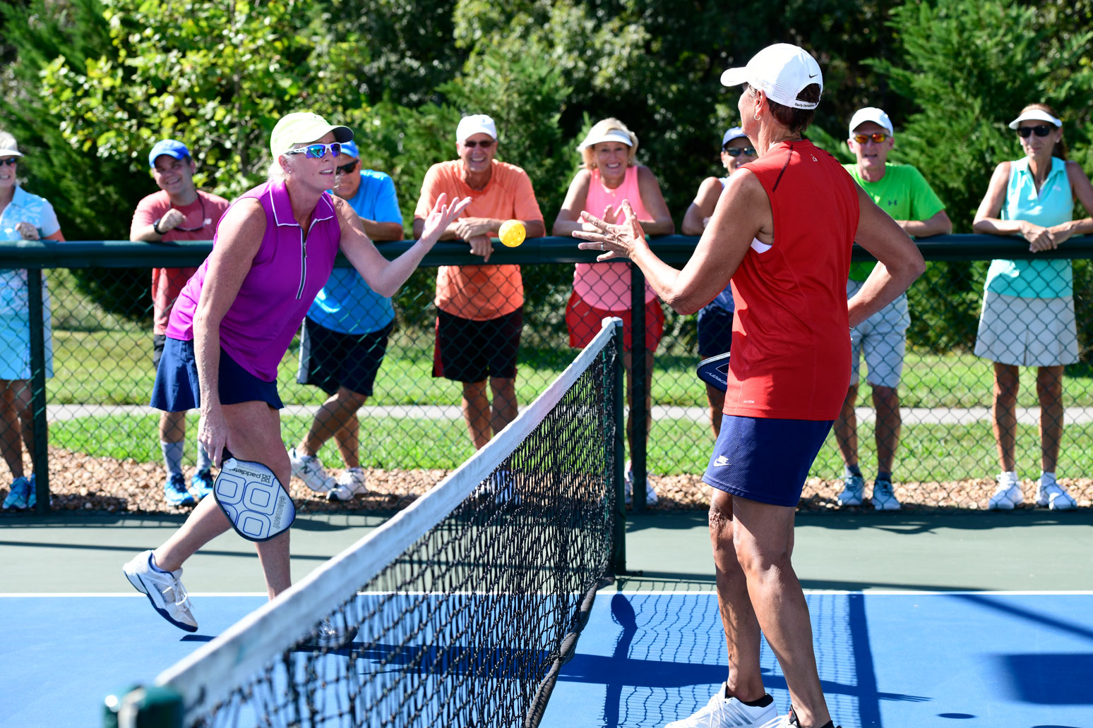 Spectators watching their fellow members of the pickleball club play a game.
