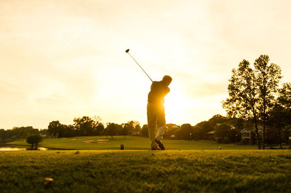 Man golfing at sunset at the Links at Kahite golf course.