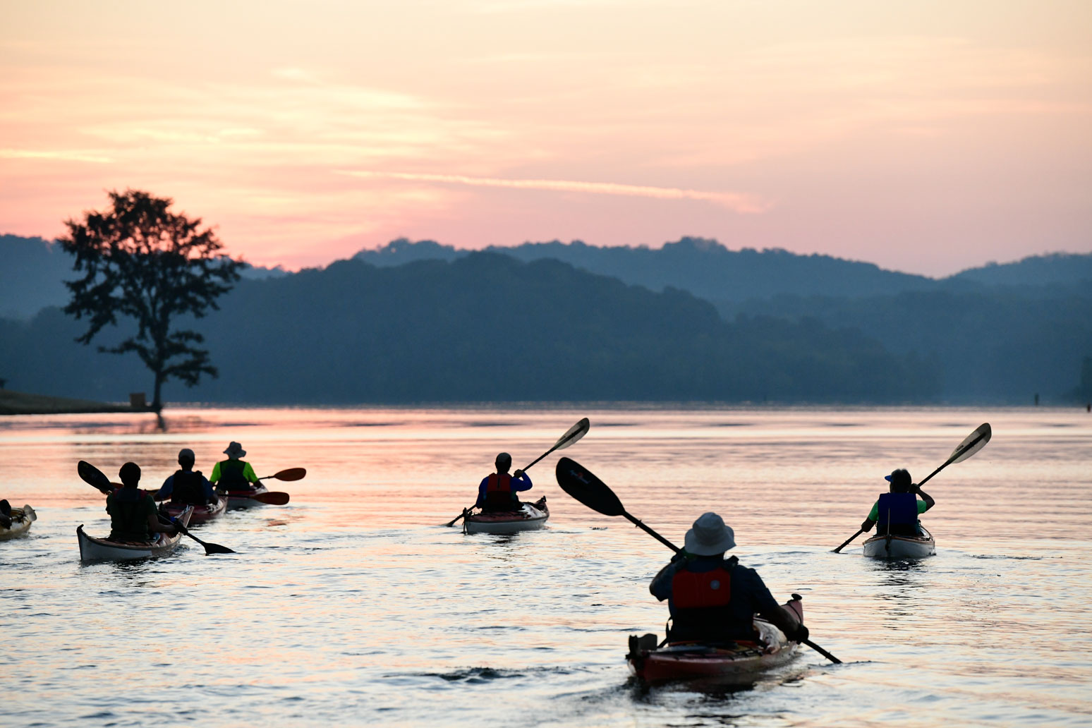 Villagers kayaking at sunrise.